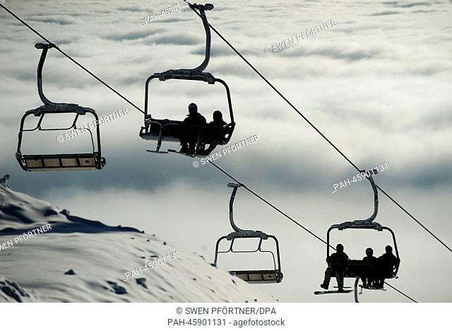 Skiers and snowboarders sit in the chairlift during the opening of the new skiing area at Wurmberg mountain in Braunlage, Germany, 25 January 2014