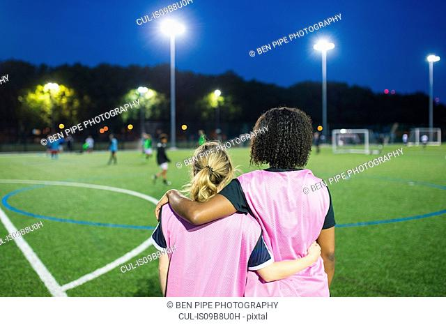 Female football players sitting by field, Hackney, East London, UK
