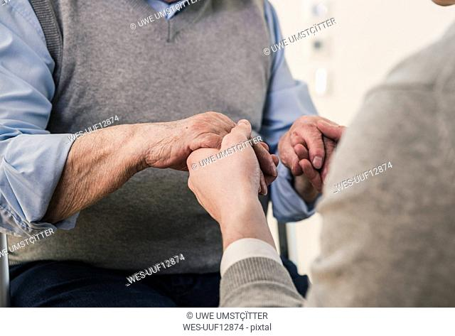 Close-up of senior man and young man holding hands