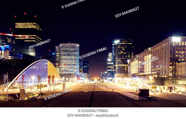 Paris city at night with business buildings and glass towers with lights, France