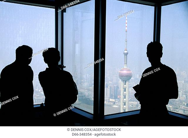 View from Jin Mao building observation deck in Pudong with Orient Pearl TV tower in foreground and Puxi area of city in background, Shanghai. China