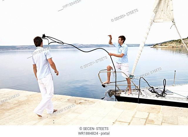 Croatia, Sailboat entering port, Two young men fixing rope