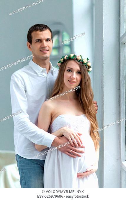 Cheerful young couple dressed in white standing against white home. Husband hugging his pregnant wife