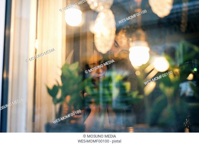 Couple in love behind window pane