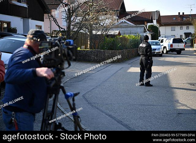 03 April 2020, Bavaria, Vogtareuth: A policeman is standing on a street in front of a house in Vogtareuth where three dead people had been found