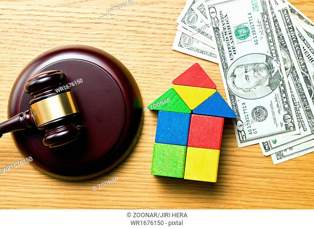 wooden house with money and judge gavel