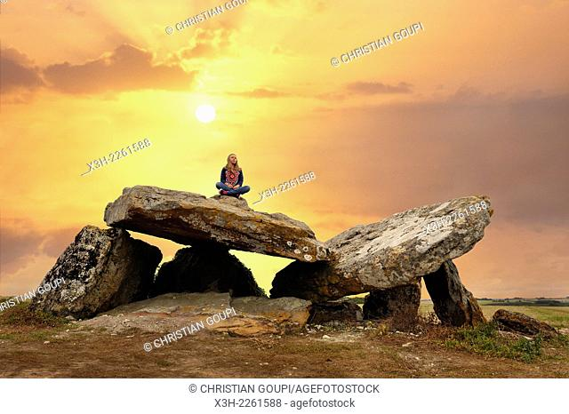 young girl sitting on a Megalithic Dolmen at sunrise, locality Le Carroir Bon Air, commune of Ligre, near Chinon and Richelieu, Indre-et-Loire department