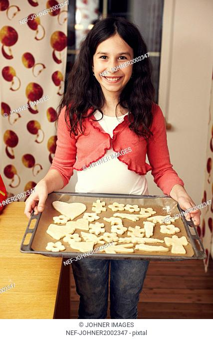 Girl holding baking tray with cookies