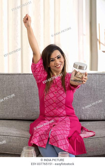 Woman cheering with jar of change