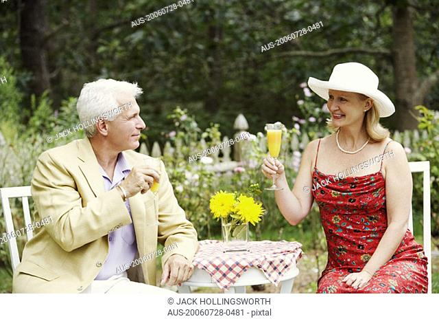 Close-up of a mature couple holding glasses of juice