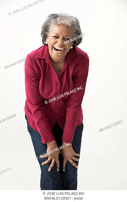 Black woman smiling with hands on knees