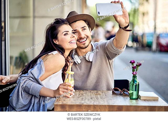 Happy young couple taking a selfie at outdoors cafe