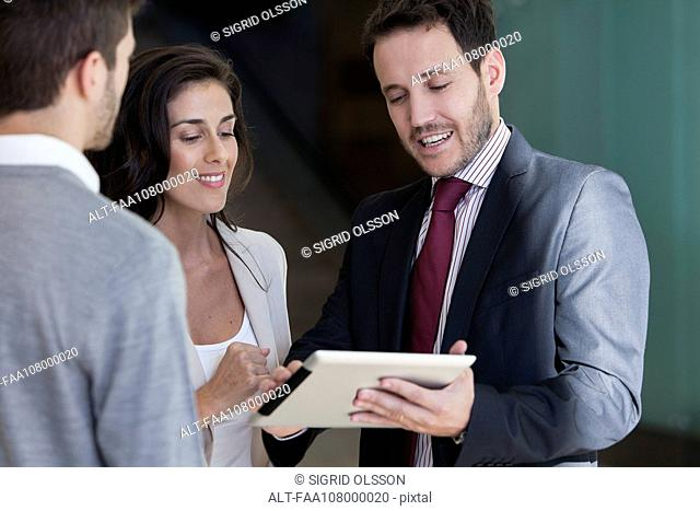 Business associates looking at proposal on digital tablet together