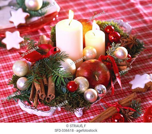 Arrangement of apples, fir sprigs, moss and baubles