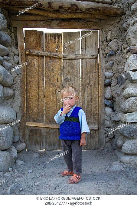 Afghan boy with blonde hair in front of a wooden door, Badakhshan province, Khandood, Afghanistan
