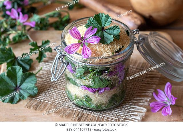 A jar filled with common mallow flowers and leaves and cane sugar, to prepare herbal syrup against cough