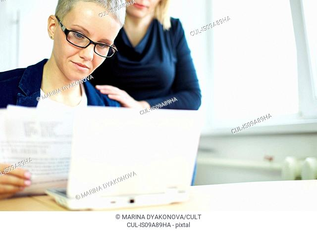 Businesswoman with paperwork with colleague's hand on shoulder