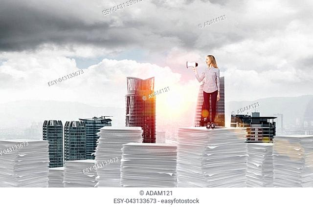 Woman in casual clothing standing on pile of documents with speaker in hand with cityscape and sunlight on background. Mixed media