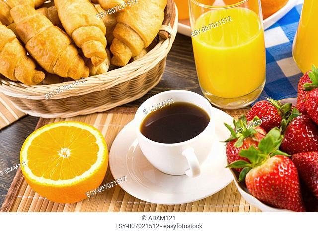 early breakfast, orange juice, coffee, croissants and strawberries