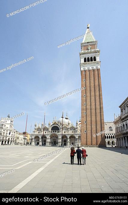 Three people from behind admire the Basilica of San Marco and the bell tower on the day of its patron, during the lockdown due to the Coronavirus pandemic...