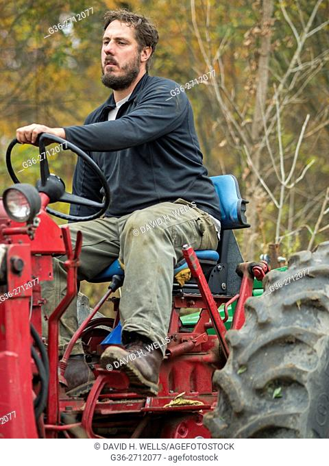 Tractor driven by small-scale farmer working on an artisanal organic farm in Johnston, Rhode Island, USA