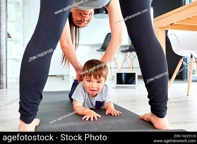 Mutter hilft Kind beim spielen und turnen auf der Gymnastikmatte im Wohnzimmer