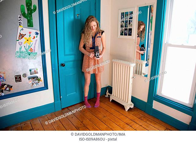 Teenager standing in bedroom with antique camera