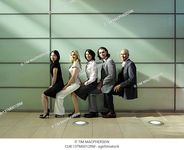 five people sitting on each other