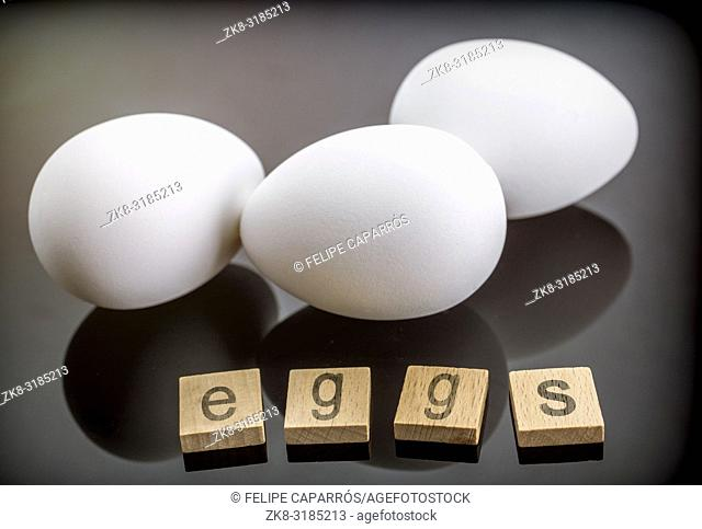 Wooden letters, several white eggs isolated on black background