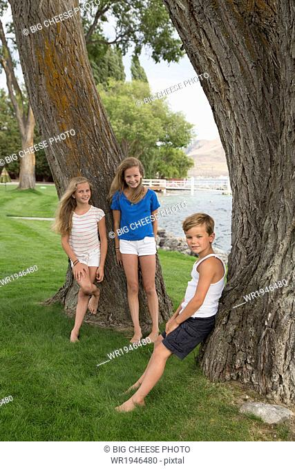 Portrait of three children by a tree near a lake