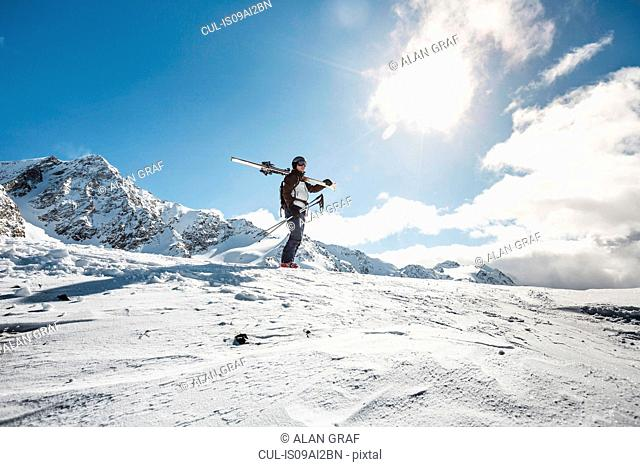 Mid adult man standing on top of mountain with skis, Corvatsch, Switzerland