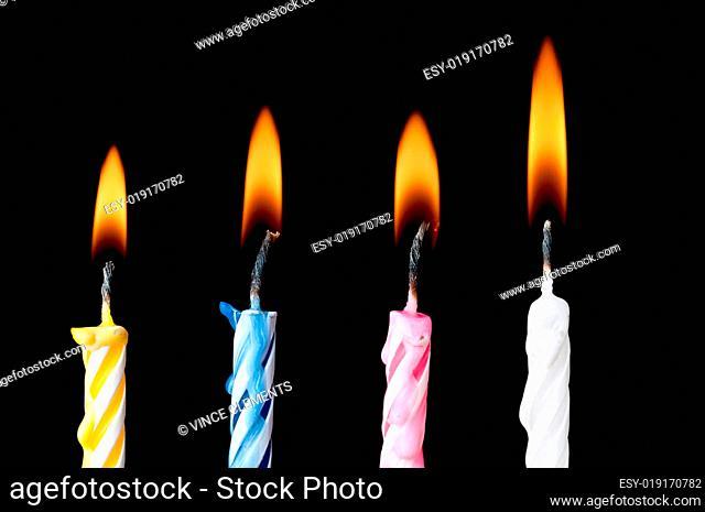 Horizontal burning birthday candles on black