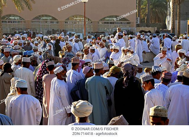 Massenszene auf dem Viehmarkt, omanischer Männer in der Nationaltracht Dishdasha und der Kummah Kappe oder dem Mussar Turban auf dem Kopf versameln sich auf...