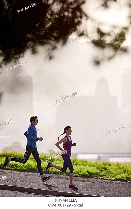 Runner couple running on sunny urban sidewalk