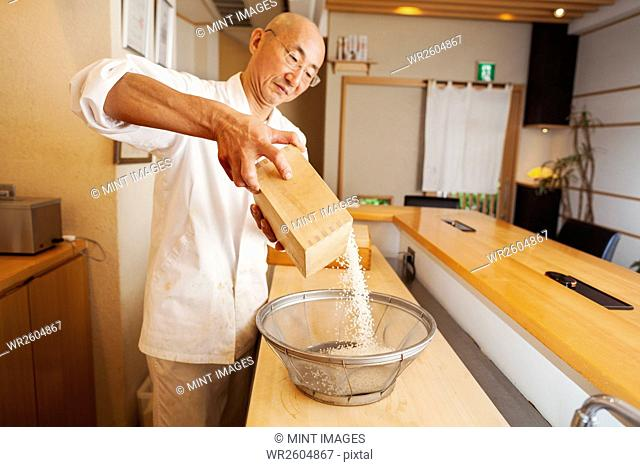 A chef working in a small commercial kitchen, an itamae or master sushi chef preparing rice for cooking