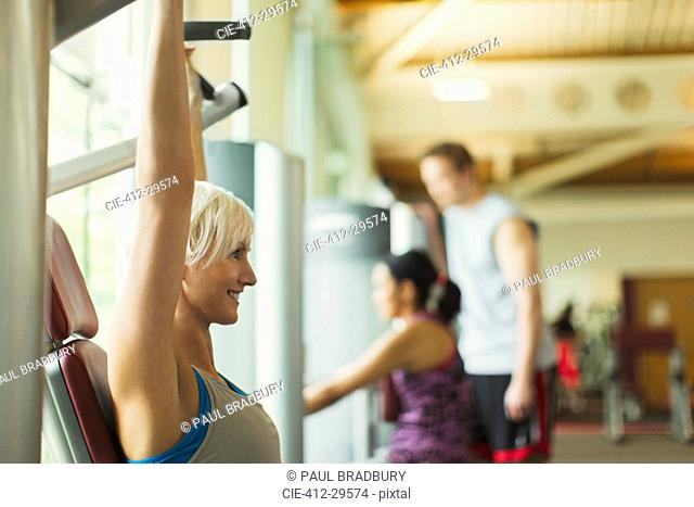 Smiling woman with arms raised using exercise equipment at gym