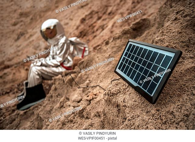 Spaceman sitting on nameless planet, charging device with solar panel
