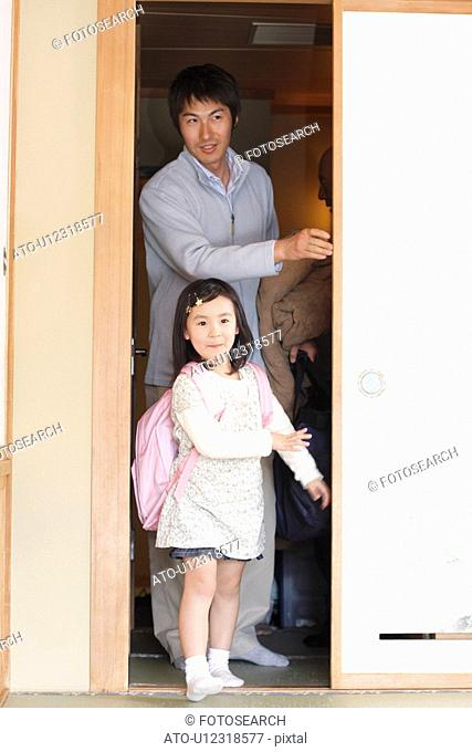 Girl with father standing at sliding door, smiling