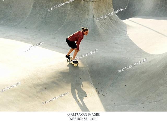 Full length of young woman skateboarding in skate park