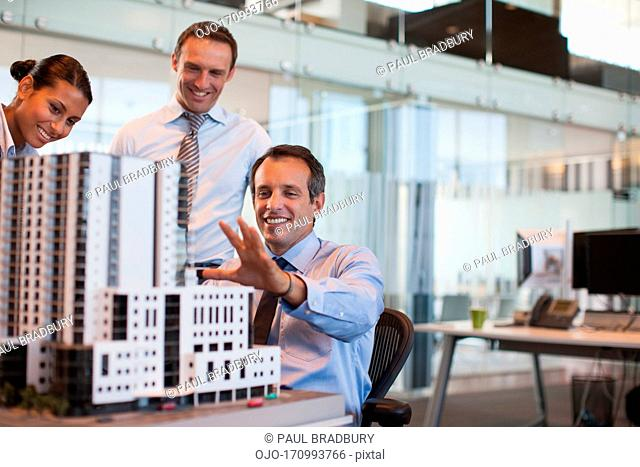 Business people looking at model building in office