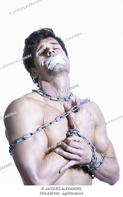 Young man tied with chain and adhesive tape
