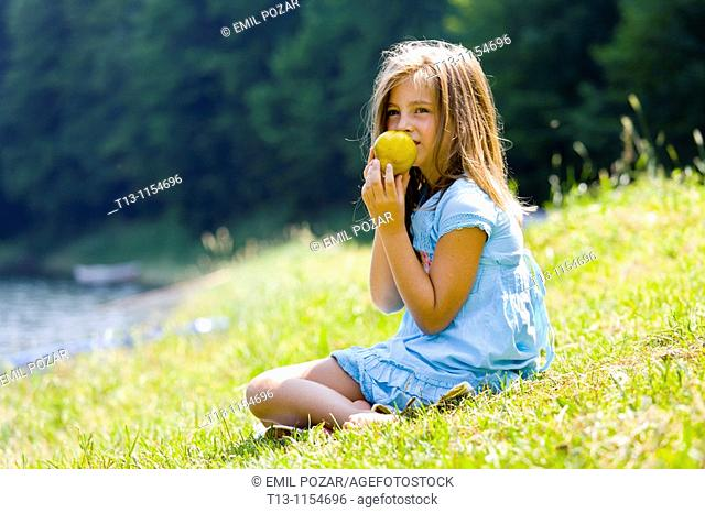 Six year old girl is eating a pear