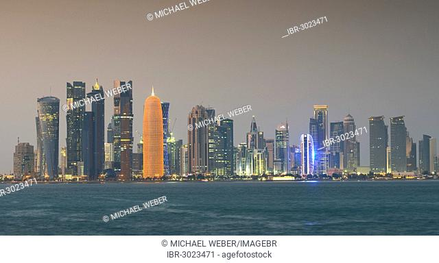 Skyline of Doha with Al Bidda Tower, Palm Tower 1 and 2, World Trade Center, Tornado Tower, Burj Qatar Tower with golden illumination
