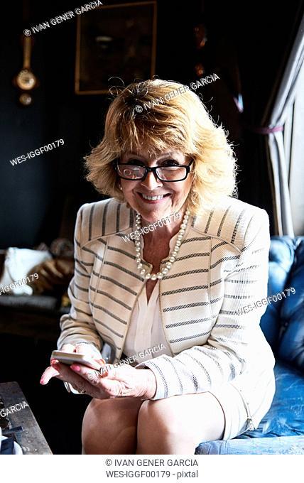 Portrait of smiling senior businesswoman holding cell phone