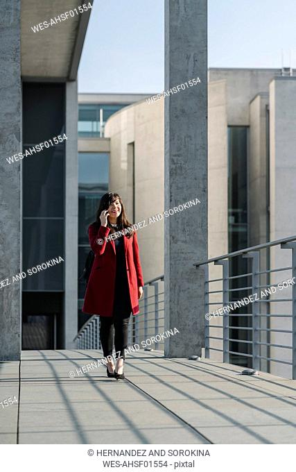 Businesswoman walking on a bridge near to modern building and using smartphone