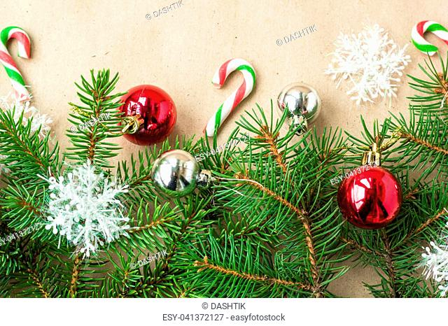 Festive christmas border with red and silver balls on fir branches and snowflakes on rustic beige background with copyspace and pen