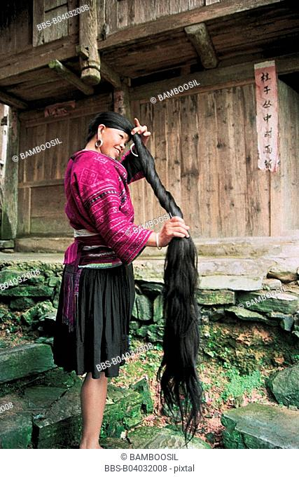 Hongyao minority long-haired girl combing, Longji mountain, Longsheng County, Guilin City, Guangxi Zhuang Nationality Autonomous Region of People's Republic of...