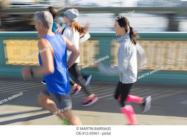 Runners running on sunny urban bridge sidewalk