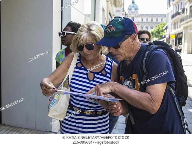 Older mature retired couple looking at a map trying to figure out their way in the streets of the city of Marseille