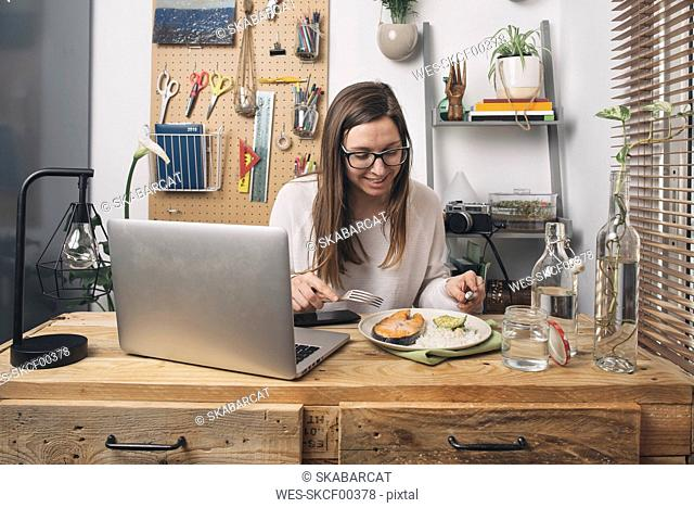 Woman having lunch at wooden table with laptop